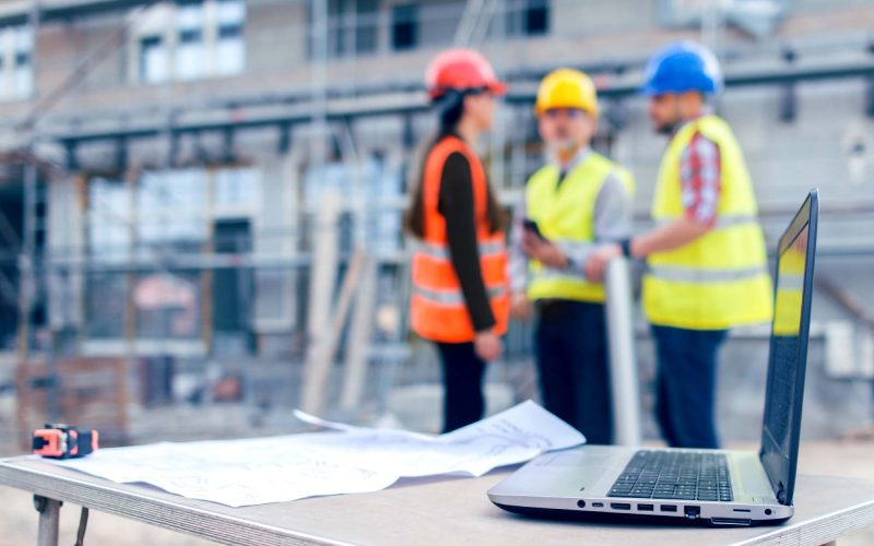 Construction workers behind blueprints and laptop on construction site